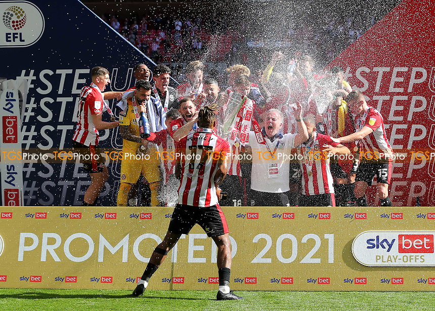Ivan Toney sprays the champagne over his teammates as Brentford celebrate winning promotion to the Premier League during Brentford vs Swansea City, Sky Bet EFL Championship Play-Off Final Football at Wembley Stadium on 29th May 2021
