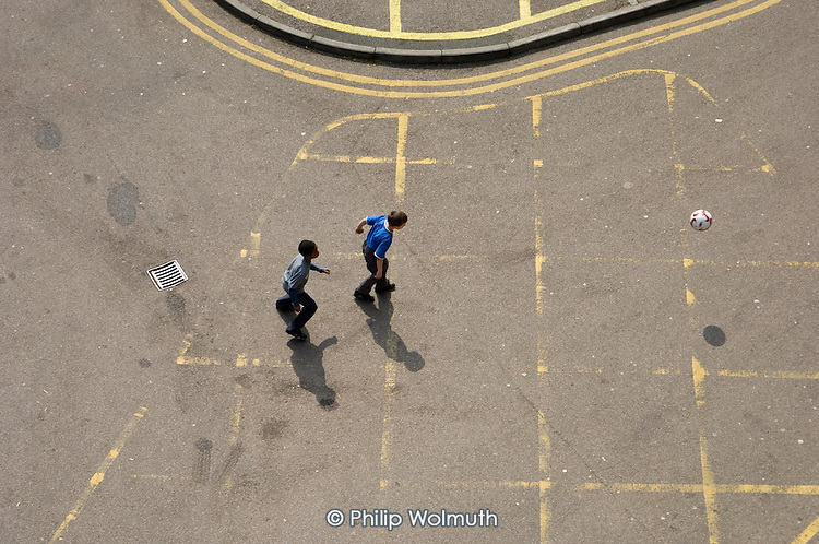 Two boys playing football in a road on Cowley Estate, Brixton, London.
