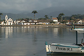 Paraty, Rio de Janeiro, Brazil. Colonial seaside port town with baroque church of Santa Rita and a wooden launch.
