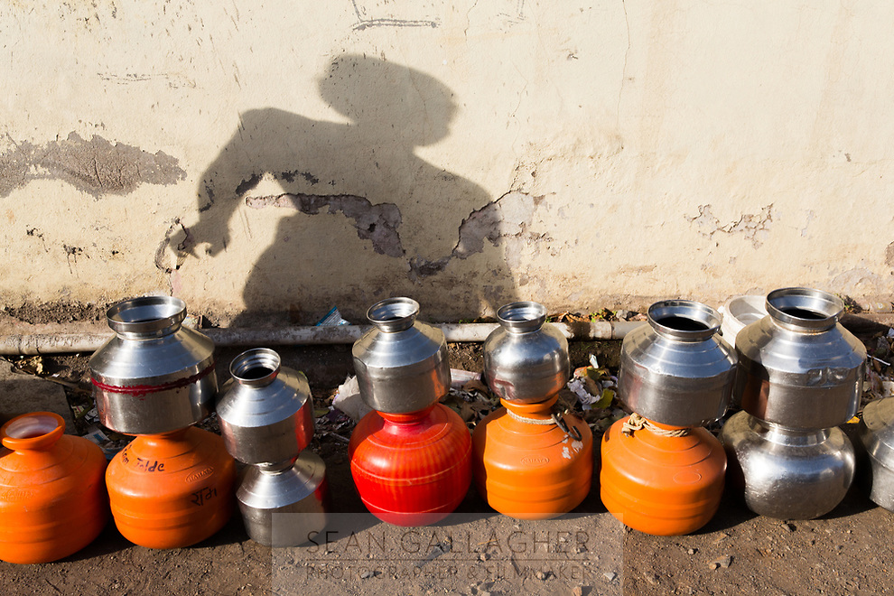 A woman's shadow falls behind a queue of pots, laid out by residents of the city of Latur, to collect water from a nearby tap which is distributing water for free to local residents.