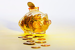 Piggy bank with coins, golden hue, glass bank with U.S. change inside.