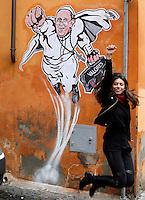 """Una turista salta di fronte ad un disegno di Papa Francesco raffigurato come Superman, realizzato dall'artista di strada Maupal (Maurizio Pallotta) e affisso da lui stesso sulla parete di un palazzo del rione Borgo, nei pressi della Citta' del Vaticano, a Roma, 29 gennaio 2014.<br /> A tourist jumps in front of a street art mural by Italian street artist Maupal (Maurizio Pallotta) depicting Pope Francis as Superman, and holding a bag reading """"Values"""" on a wall of the Borgo district near the Vatican, in Rome, 29 January 2014.<br /> UPDATE IMAGES PRESS/Riccardo De Luca<br /> <br /> STRICTLY ONLY FOR EDITORIAL USE"""