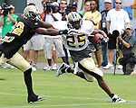 Reggie Bush provides a stiff arm as he runs to the outside during New Orleans Saints training camp.
