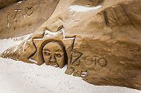 """Most """"beach art'"""" is limited to building sand castles and drawing in the sand, but here is an example of stone carving in the bluffs.  The sandstone bluffs easily yield to simple tools - as easily as they yield to the surf that comes with hightide.  These artistic creations, carved in stone, likely won't survive a year's worth of hightides.  But till then, until they're gone, art lives in stone along the California Coast."""