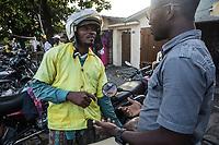 conduttore di moto taxi discute con un cliente
