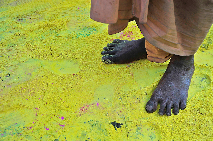 Feet on yellow Holi powder during the Holi festival in Jaipur, Holi is celebrated all over India,
