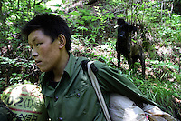 A young man and his dog in the Jiuzhaigou National Park. Sichuan Province. China.