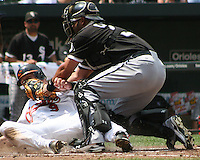 Ramon Castro #27 of the Chicago White Sox tags out Jake Fox #9 of the Baltimore Orioles during a MLB game at Camden Yards, on August 8 2010, in Baltimore, Maryland.