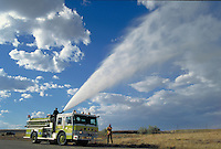 A Casper, Wyoming firetruck waters dry grass on a sunny day. Casper Wyoming USA.