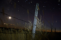 A barbed wire fence stands in the night on a farm north of Rudyard, Montana, USA.