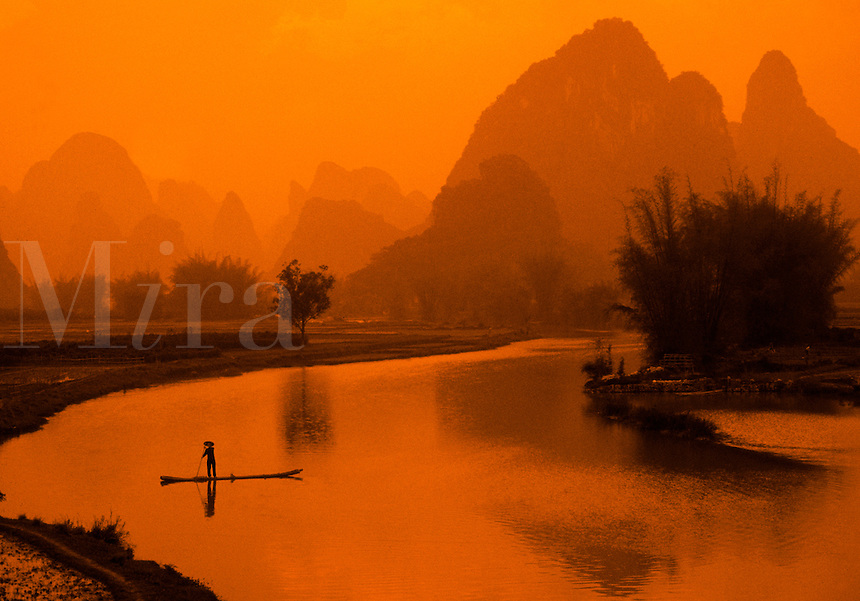 Moody landscape of the Guilin Yangshou Li River with mountains in the background; a fisherman on a raft in silhouette in the foreground. China.