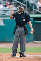 Home plate umpire Roberto Medina indicates he needs four baseballs during a Florida State League game between the Charlotte Stone Crabs and the Jupiter Hammerheads at Roger Dean Stadium June 15, 2010, in Jupiter, Florida.  Photo by Brian Westerholt /  Seam Images
