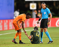 LAKE BUENA VISTA, FL - JULY 18: Alberth Elis #7 of the Houston Dynamo tries to assist Jorge Villafaña #4 of the Portland Timbers to his feet after committing a foul as the referee Ismail Elfath looks on during a game between Houston Dynamo and Portland Timbers at ESPN Wide World of Sports on July 18, 2020 in Lake Buena Vista, Florida.