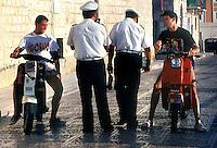 Vigili urbani mentre controllano dei ragazzi senza casco con i motorini..policemen during a control to boys without helmets with motorcycles...