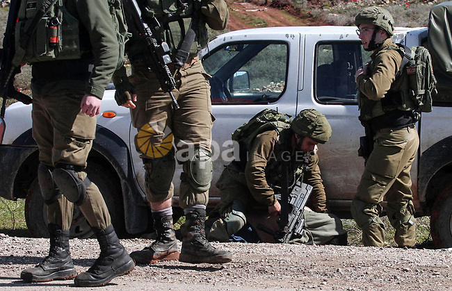 Israeli soldiers arrest a Palestinian protester during protest against bulldozing operations carried out by the occupation bulldozers near the village of Aqraba, south of the West Bank city of Nablus on March 3, 2020. Photo by Ayman Nobani/ WAFA