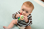 5 month old baby boy siting closeup looking up holding and mouthing wooden toy with colorful balls attached