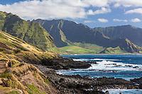 Two hikers on Ka'ena Point Trail and coastline, with Yokohama Bay and Makua Valley in the background, West O'ahu.