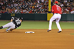 Brent Morel of the Chicago White Sox, slides past second base as Brandon Wood of the Angels looks on.