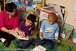 Preschool Headstart 3-5 year olds female teacher reading to and working with boy as another boy looks at a book nearby horizontal