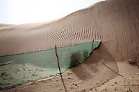A fence disappears into a sand dunes in Hebei Province, China. Desertification is the process by which fertile land becomes desert, typically as a result of drought, deforestation, or inappropriate agriculture. 41 % of China's landmass in classified as arid or desert. Inappropriate farming methods and over cultivation have contributed to the spreading of deserts in China in recent years.