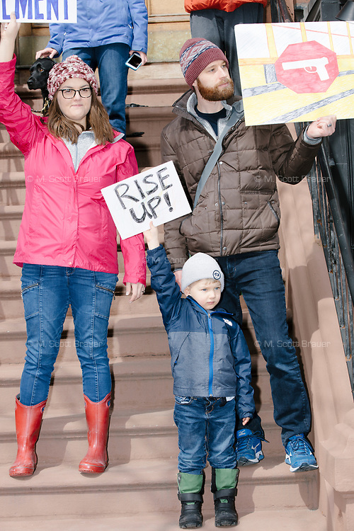 """A family holds signs, including one reading """"Rise up!"""" from a stoop while People take part in the March For Our Lives protest, walking from Roxbury Crossing to Boston Common, in Boston, Massachusetts, USA, on Sat., March 24, 2018, in response to recent school gun violence."""