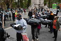 NEW YORK, UNITED STATES - NOVEMBER 21: Activists protest using body bags for Trump administration moves as overturn the election, his Covid Program and whipping up MAGA fascist mobs and  the deportation of undocumented immigrants in Trump international Hotel on November 21, 2020 in New York City. Some people gather in Columbus Circle to protest against the government of President Donald Trump, with a symbolic act where they use black bags as if they were corpses due to the thousands of deaths produced by Covid-19. Photo by Joana Toro / VIEWpress via Getty Images)