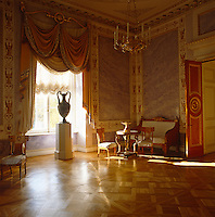 The Corner Drawing Room and former bedroom of Paul I was created by Carlo Rossi and features violet and lilac toned stucco panels with painted borders