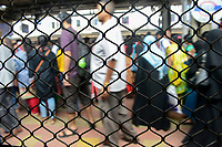 INDIA, Mumbai, suburban railway station of commuter train Western Railway WR, commuter travel between suburbans and city centre, view from barred train window