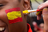 A spain fan has her face painted