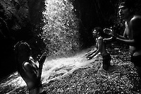 Young Ecuadorean men (Hare Krishna followers) worship the spirit of water during the private ritual held in the cave of Peguche waterfall, Ecuador, 24 June 2012.
