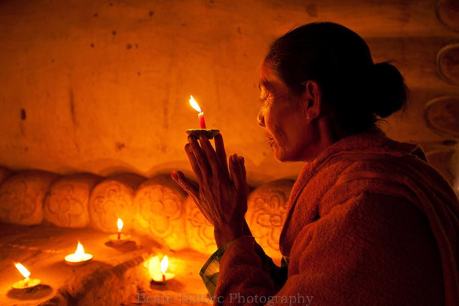 Woman worshipping at the feet of the reclining Buddha in the Shinbinthalyaung temple, Bagan, Myanmar