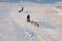 Bruce Linton runs in front of Paul Gebhart on the Unalakleet slough ice after leaving Unalakleet in Arctic Alaska during the 2010 Iditarod
