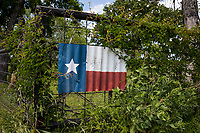 Rustic flag of Texas painted on corrugated metal sign on a country barbed wire fence.
