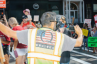 """A man wearing a reflective vest with Qanon symbols including the letter Q over an American flag and the letters WWG1WGA, which stands for """"Where we go one, we go all,"""" speaks to a reporter as people gather outside the Massachusetts State House for the No Mandatory Flu Shot MA demonstration in Boston, Massachusetts, on Sun., Aug. 30, 2020. The protest was organized in opposition to a newly-enacted law requiring most children in Massachusetts to receive flu vaccines this year as part of public health efforts during the ongoing Coronavirus (COVID-19) global pandemic. Some of those involved in this protest have been involved in the right-wing pro-Trump, pro-reopening protests organized by Super Happy Fun America during spring and summer 2020."""