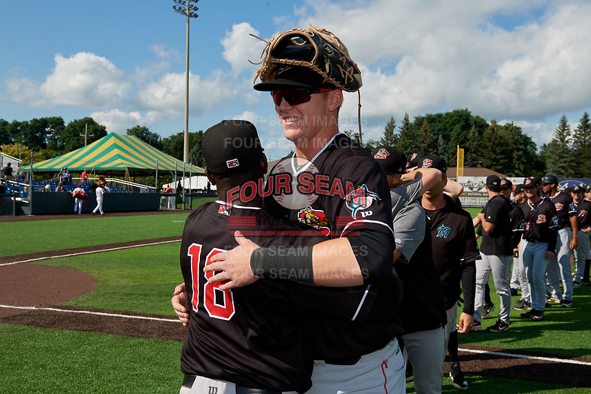 Batavia Muckdogs hitting coach Rigoberto Silverio (18) hugs Sean Reynolds (25) after clinching the Pinckney Division Title during a NY-Penn League game against the Auburn Doubledays on September 2, 2019 at Falcon Park in Auburn, New York.  Batavia defeated Auburn 7-0 to clinch the Pinckney Division Title.  (Mike Janes/Four Seam Images)