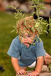 A young toddler hides behind the branch of a tomato plant after he picked a tomato.