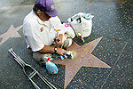 Hollywood Entertainment District representative cleans and polishes the stars on the Hollywood Walk of Fame, Hollywood, CA