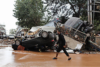 Pictured: A man walks past cars wrecked by the flooding.<br /> Re: Five people have reportedly died and severe damage caused by heavy rain and flash flooding in the area of Mandra, near Athens, Greece. Wednesday 15 November 2017