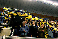"""Beitar Jerusalem soccer fans draped in the team's black-and-yellow colours support their team during the match for the league against Hapoel Tel Aviv in the Jerusalem stadium """"Tedy"""". Hapel Tel Aviv is considered by Betar fans  the worst enemy in the league which represents the Ashkenazy (European born) lefty club.  Beitar won the match 2 -1. Beitar Jerusalem FC was founded in the 1930's by the right-wing Revisionist Zionist movement, which later formed the Israeli Likud political party, during the British Mandate rule over Palestine. The chanting of the club is racist and mainly against Arabs. The team is the only one in the Israeli league to have never had an Arab player. Beitar is seen as the right wing and Mizrahi (Jews who came from Asia and Africa) club. Photo by Quique Kierszenbaum"""