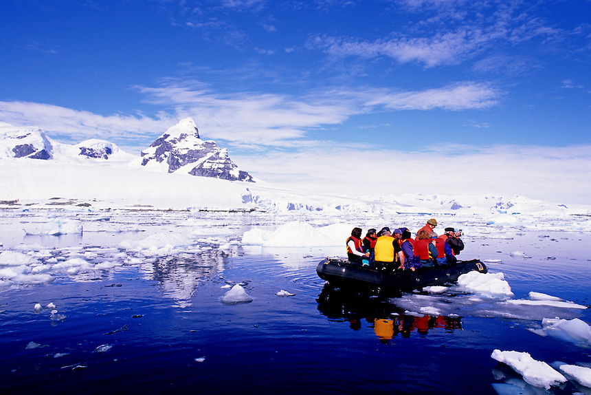Tourists sightseeing glaciers from a Zodiac, Prospect point, Antarctica.