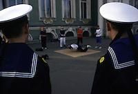 San Pietroburgo, due marinai, di schiena, osservano dei giovani che danzano, breakdance