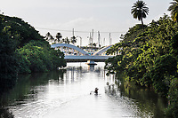 A one-man outrigger canoe on Anahulu River, with Hale'iwa Small Boat Harbor and the Rainbow Bridge in background, North Shore, O'ahu.