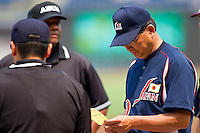 Japan Head Coach Koji Kanemitsu #30 goes over his lineup card prior to the game against the USA Baseball Collegiate National Team at the Durham Bulls Athletic Park on July 3, 2011 in Durham, North Carolina.  USA defeated Japan 7-6.  (Brian Westerholt / Four Seam Images)