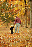 Father and child walking in woods.