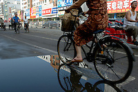 Woman riding a bicycle alongside scooters on a busy city street, Datong, Shanxi, China.