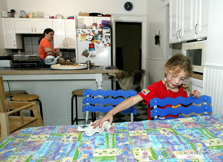 Foster parent Bobbi Pedersen, left, cleans up after dinner as her adopted daughter Aleah Pederson finishes wiping off the dinner table Monday June 16, 2003 in Columbus, Ohio.<br />