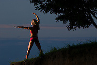 Woman athlete stretches at sunrise