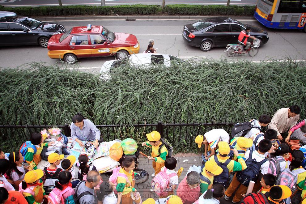 CHINA. Beijing. Schoolchildren coming out of school in central Beijing. 2009
