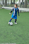 Soccer 8 year old girl practicing on field near goal