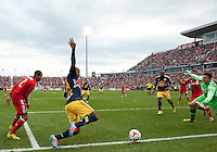 Toronto, Ontario - May 17, 2014: New York Red Bulls forward Thierry Henry #14 attempts to kick a ball past Toronto FC goalkeeper Joe Bendik #12 during the second half in a game between the New York Red Bulls and Toronto FC at BMO Field. Toronto FC won 2-0.